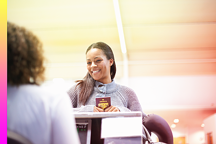 Woman at a check-in desk holding passport