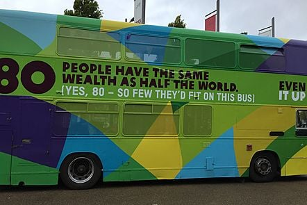 Colourful bus with '80 people have the same wealth as half the world' written on it.