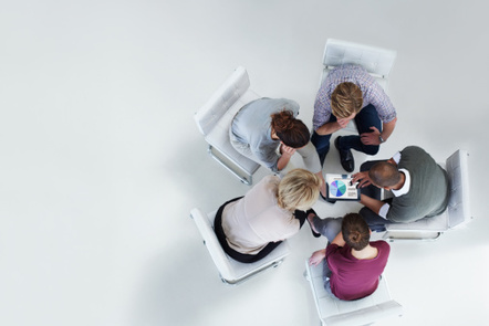 Top down view of 4 people sat round table with laptop