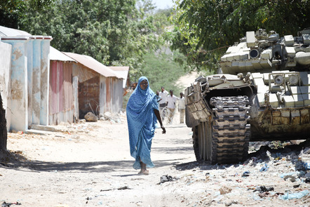 A woman walks past an AMISOM tank in the village of Jamuhuria near the frontline with Al Shabaab.