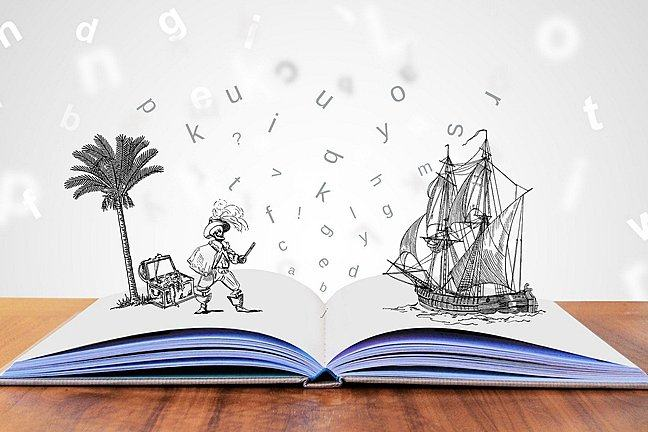 An open book with letter flying off as well drawings of a pirate, a treasure and a pirate boat