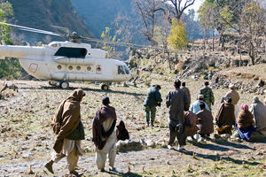 Group of tribespeople in a mountaneous region awaiting by the parked helicopter.