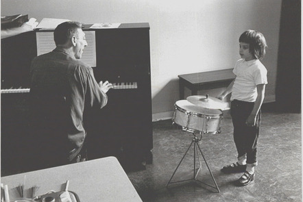 A black and white archive photo of Paul Nordoff playing a piano while a young child is standing playing a drum
