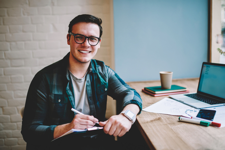 A young man with glasses smiles at the camera. He has a pen in his hand and a notebook in his lap, with a laptop, markers, paper and a coffee on the table beside him.