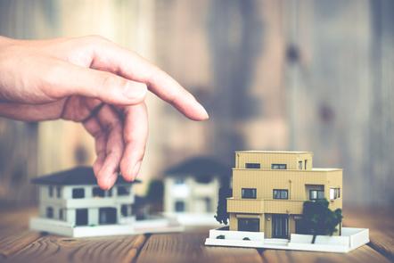A hand pointing towards a cardboard cutout of a house.
