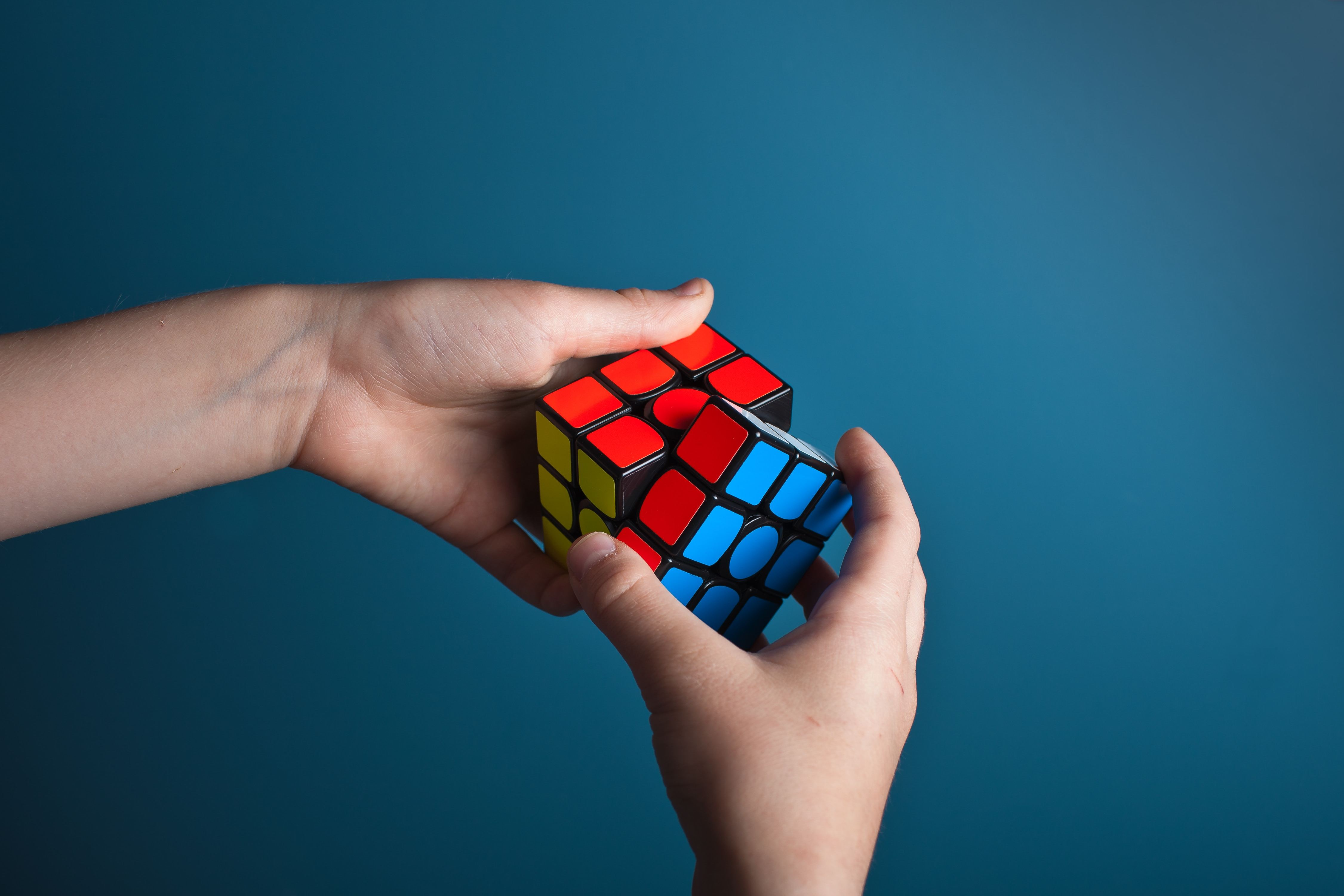 Two hands holding a Rubik's cube puzzle that's about to be solved.