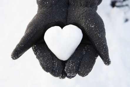 Heart-shaped snow held in woman's gloved hands
