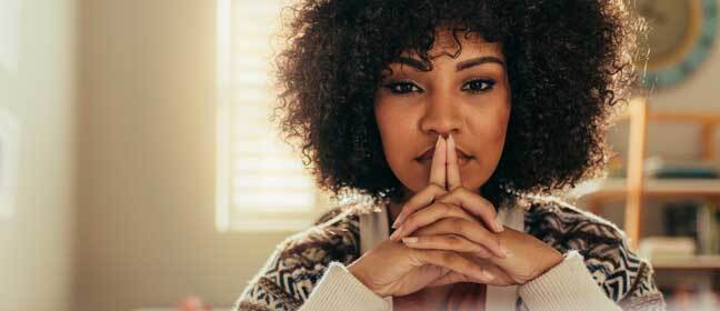 Woman thinking with her hands clasped in front of her lips.