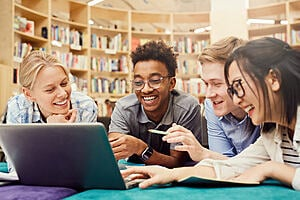 smiling students sat around a laptop in a library