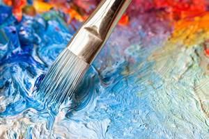 Un pincel mezcla pinturas coloridas.