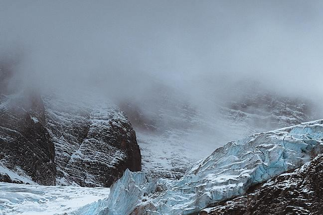 Moody image of mountains shrouded in cloud, with a glacier in the foreground.