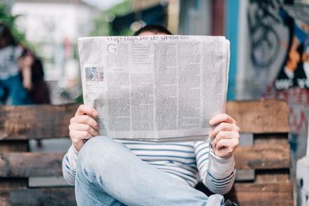 Person sat on a bench reading a newspaper