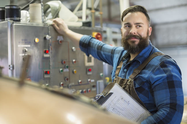 Confident brewery worker at control panel