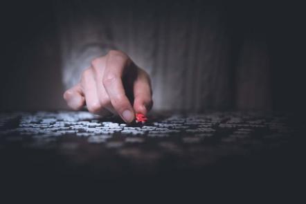 Man holding a red jigsaw piece.