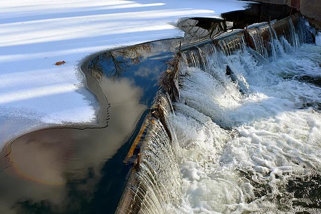 Image of water pouring over a dam from a large, ice-covered river.