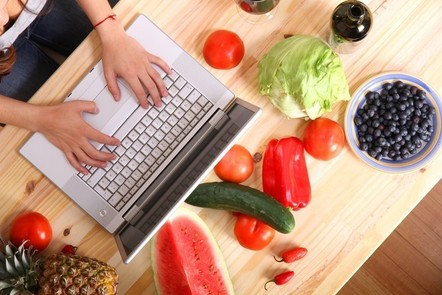 A woman working on a laptop, surrounded by fruit and vegetables