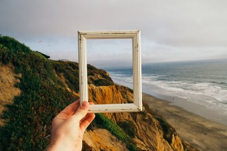Person holding a photo frame over a landscape view