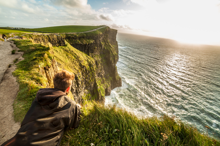 A young man sitting at the Cliffs of Moher.