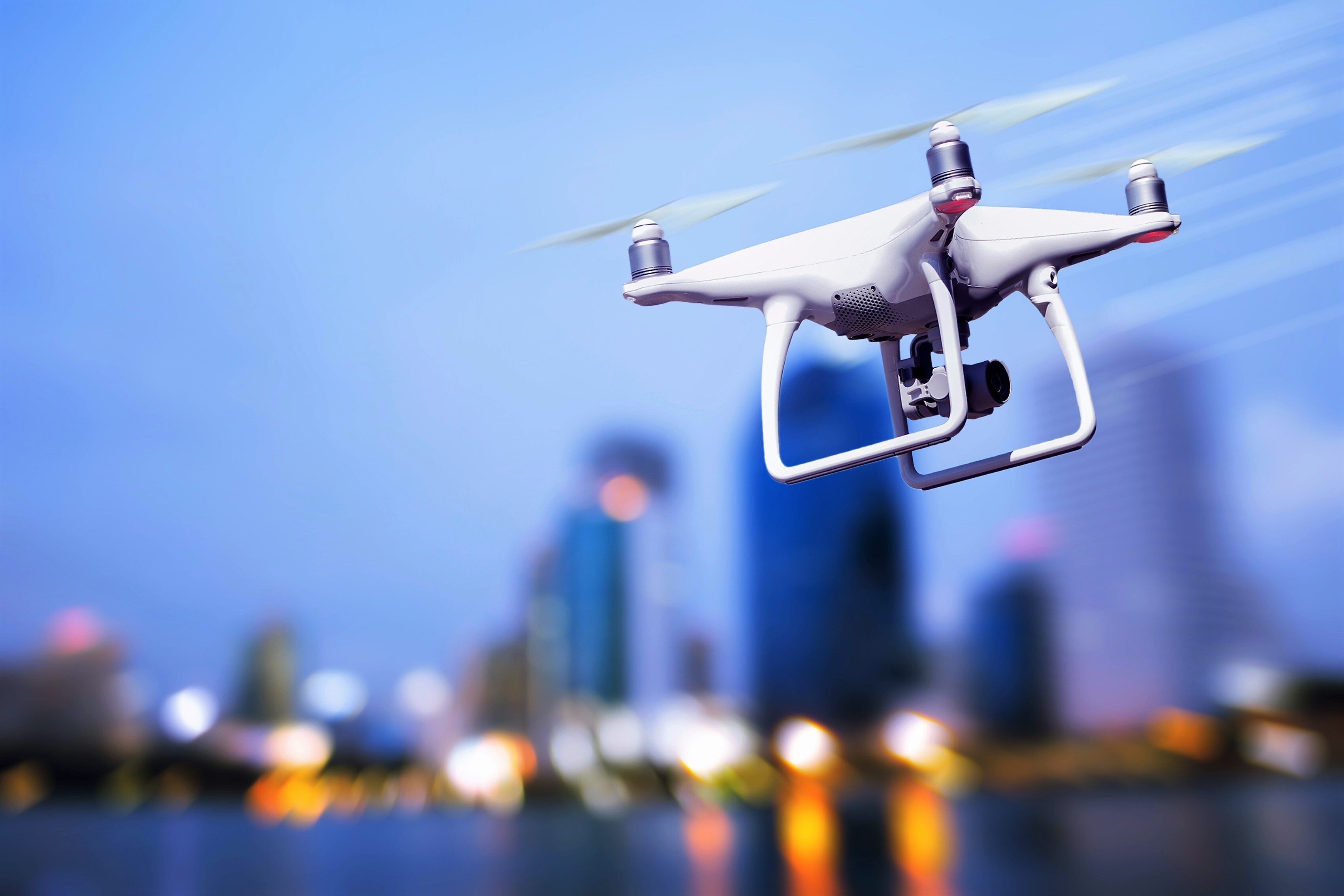 a white drone in flight across a city at dusk