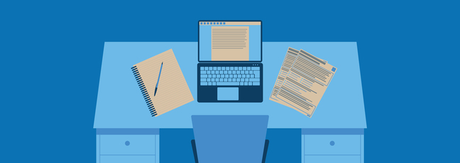 A desk during the application process with computer, note pad and CV