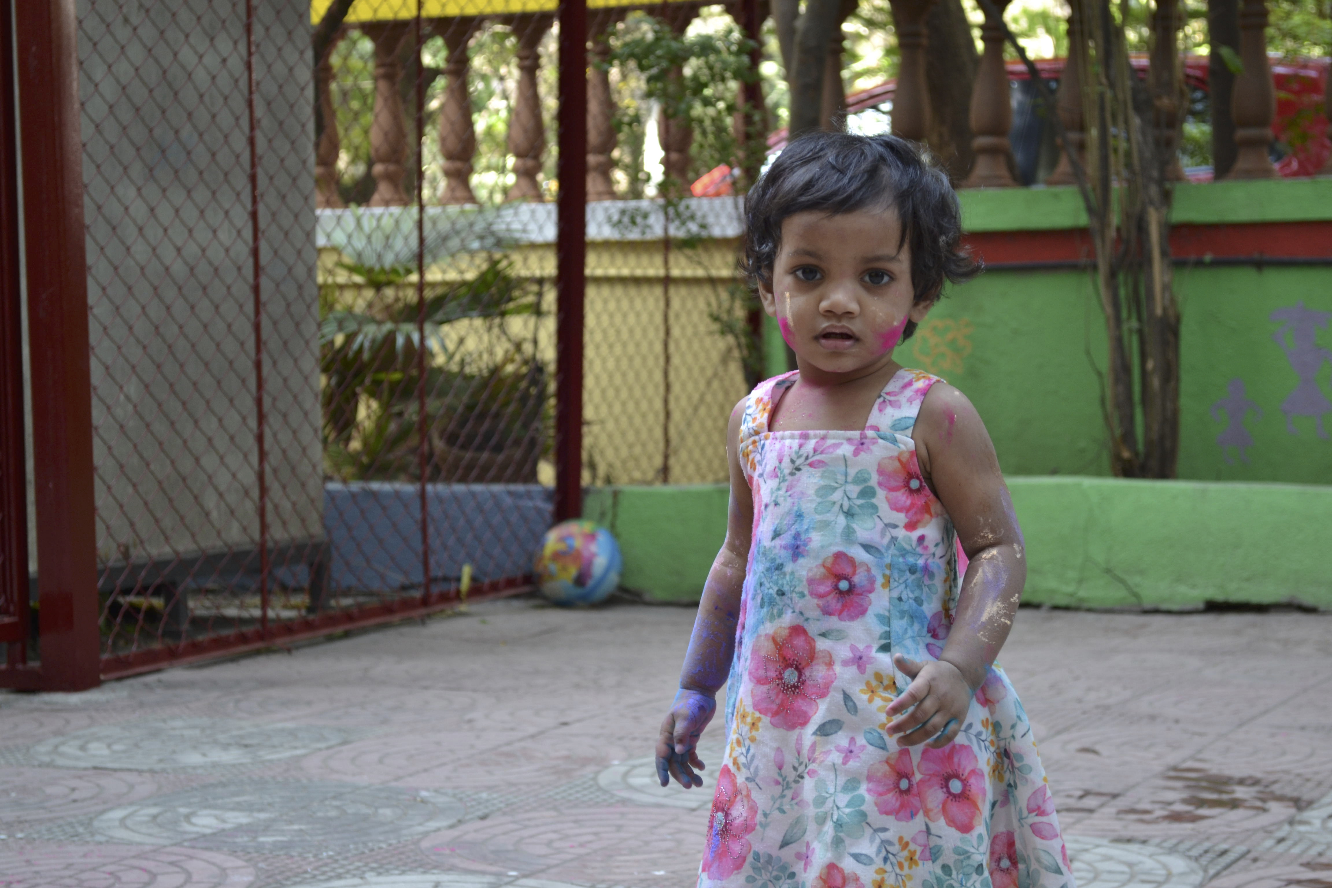 A young girl wearing a flower patterned dress is covered in paint, having played in a playground