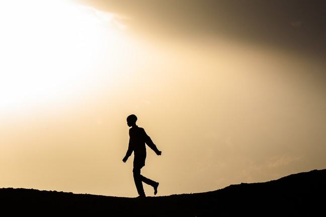 A silhouette of a boy with a long shirt and long pants walking on top of a hill.