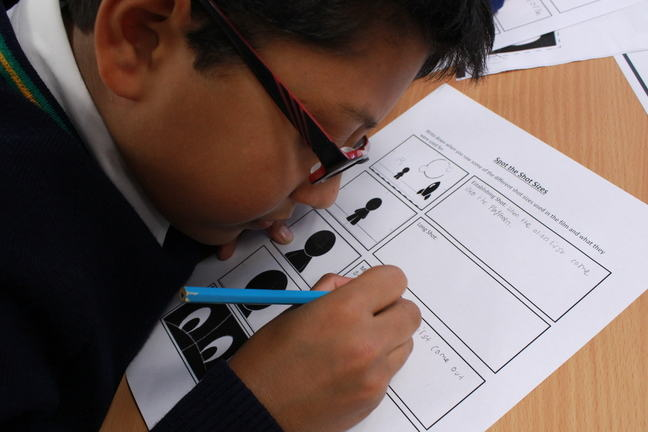 Child in classroom filling in camera shots worksheet