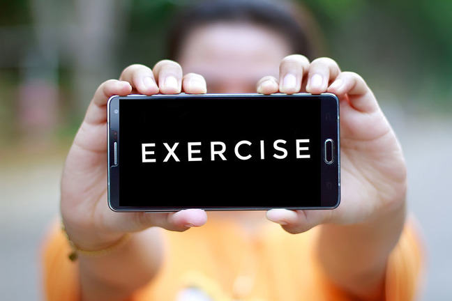 Person holding a mobile phone showing the word exercise