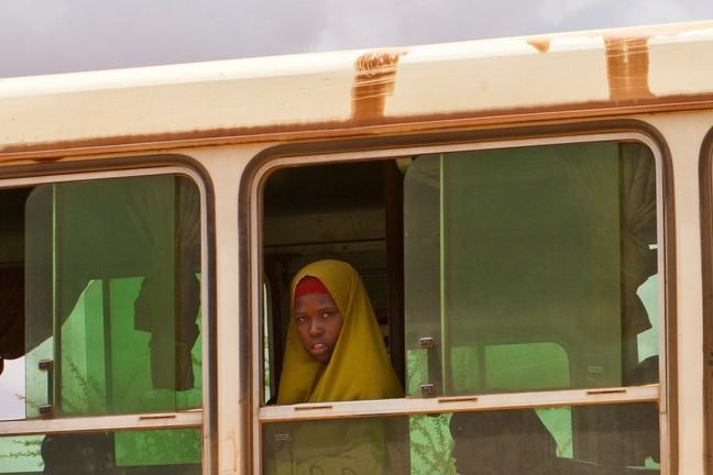 A young African girl with yellow material covering her head and shoulders is standing in a bus looking out of the window. There are silhouettes of other children in the bus sitting nearby.
