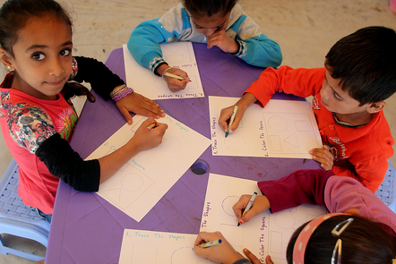 A group of primary school children sitting at a table, colouring shapes