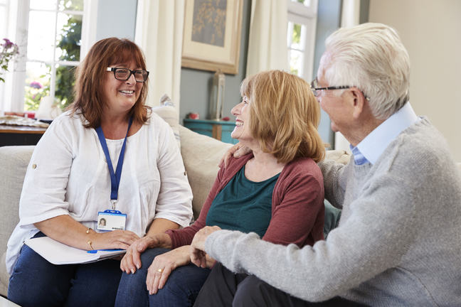 A healthcare worker sitting on a couch talking to an older couple.