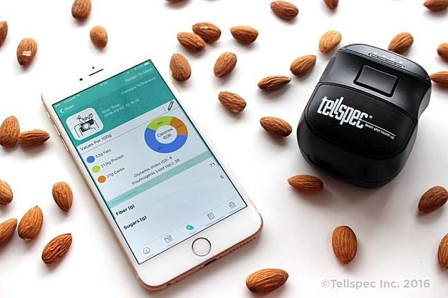 Photograph of a Tellspec sensor alongside a smartphone displaying the Tellspec app on a white background with nuts scattered around