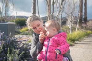 The photo is of a female cancer patient walking on a garden path holding her young infant daughter. In the photo, the patient is holding a flower up to her daughter's nose.