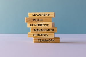 Stack of wooden blocks with Leadership, Vision, Confidence, Management, Strategy and Teamwork stamped on them