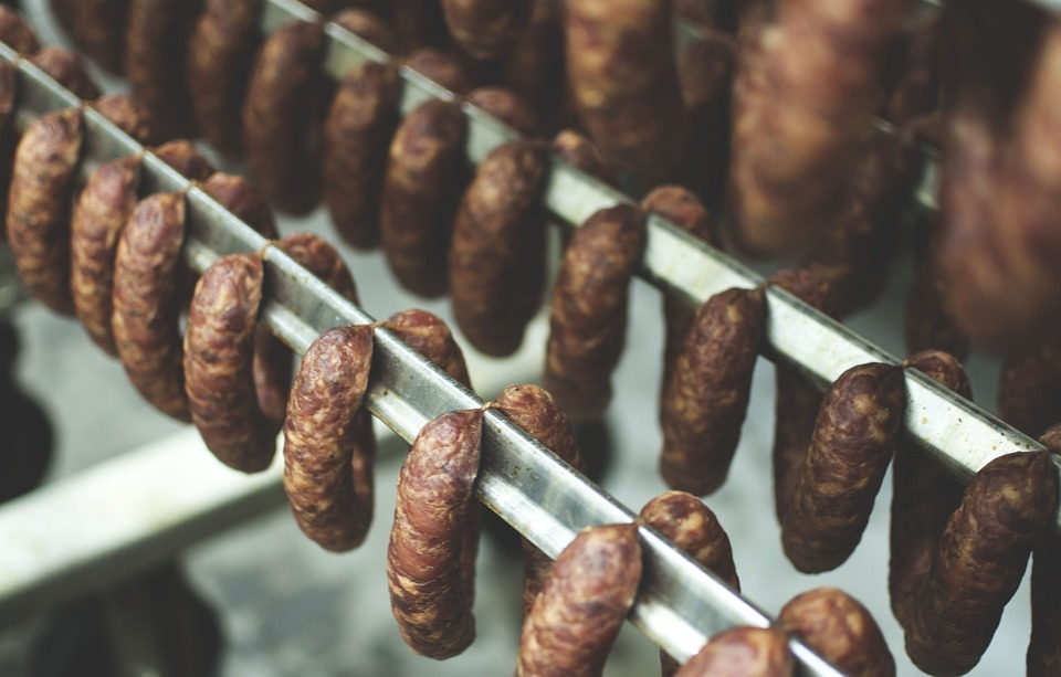 Traditional sausage smoking - paired sausages hanging on metal racks in a smokery