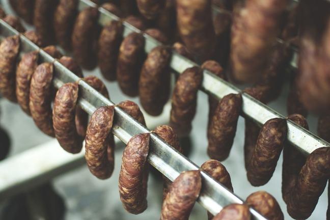 Traditional sausage smoking - paired sausages hanging on metal racks in a smokery