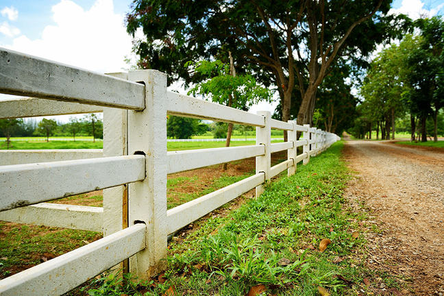 The image is of a white fence showing the boundary of a field it encompasses.