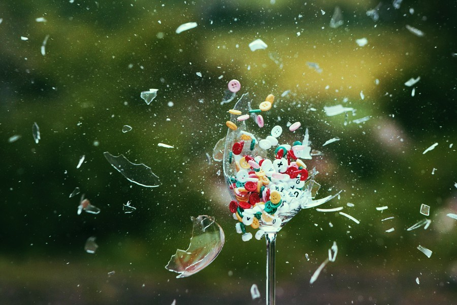 An exploding wine glass full of buttons and letters