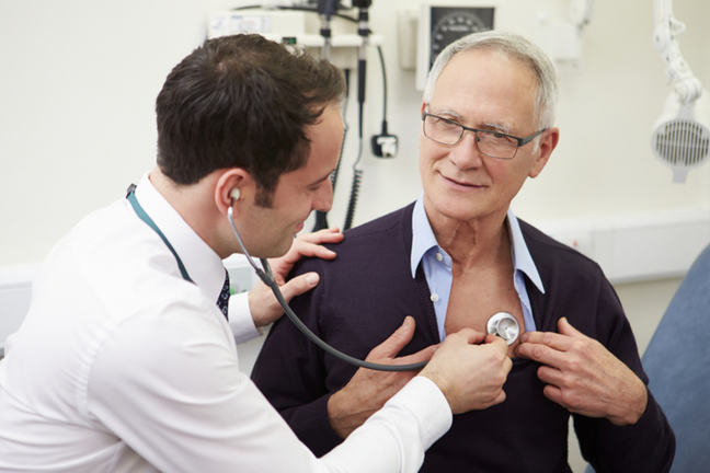 A doctor listening to a man's chest using a stethoscope.