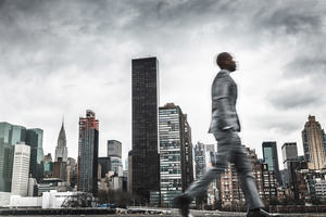 A businessman walking through a cityscape.