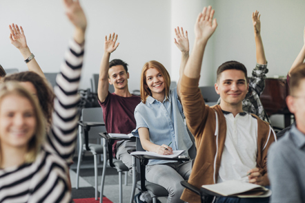 Group of high school students sitting in a classroom raising their hands