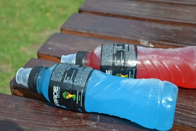 Two commercially available sports drinks, one containing a blue liquid, the other red.