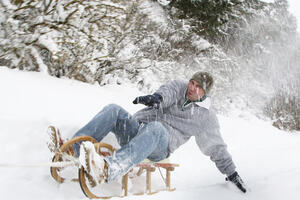 A man on a wooden sledge in the snow reaching out his arms to find his balance.