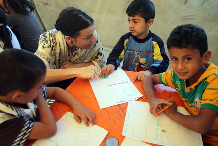 A female teacher working with a group of young children