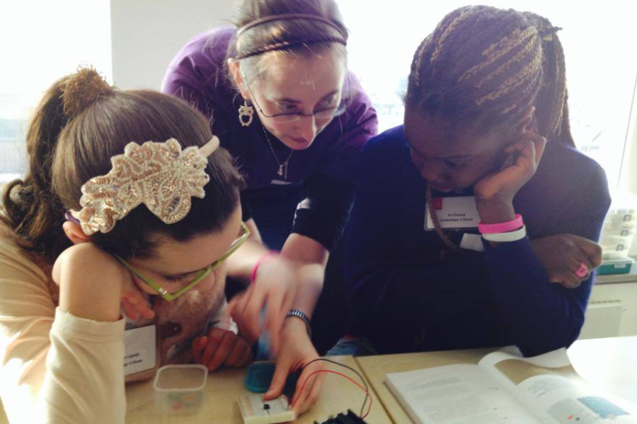 A woman showing two girls some electronics.