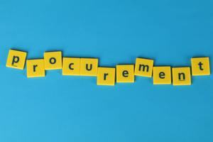 The word procurement spelt in Scrabble tiles.