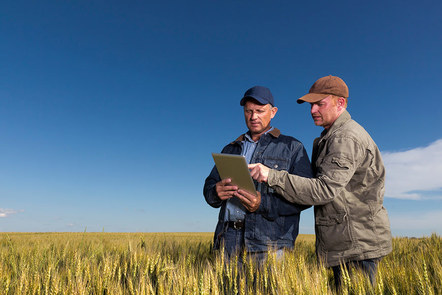 Two men standing in a field looking at a tablet smart device.