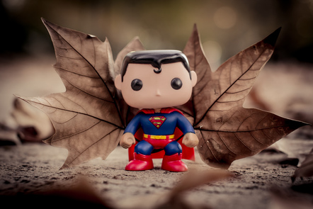 Photo of a miniature figurine of the character Superman standing in front of two brown maple leaves.