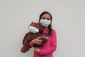 Young girl holding a brown teddy. Both are wearing a face mask.