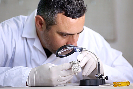 Man checking jewellery through a magnifying glass.